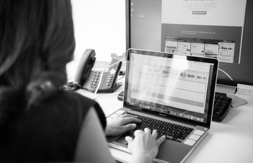 grayscale photo of person using laptop computer